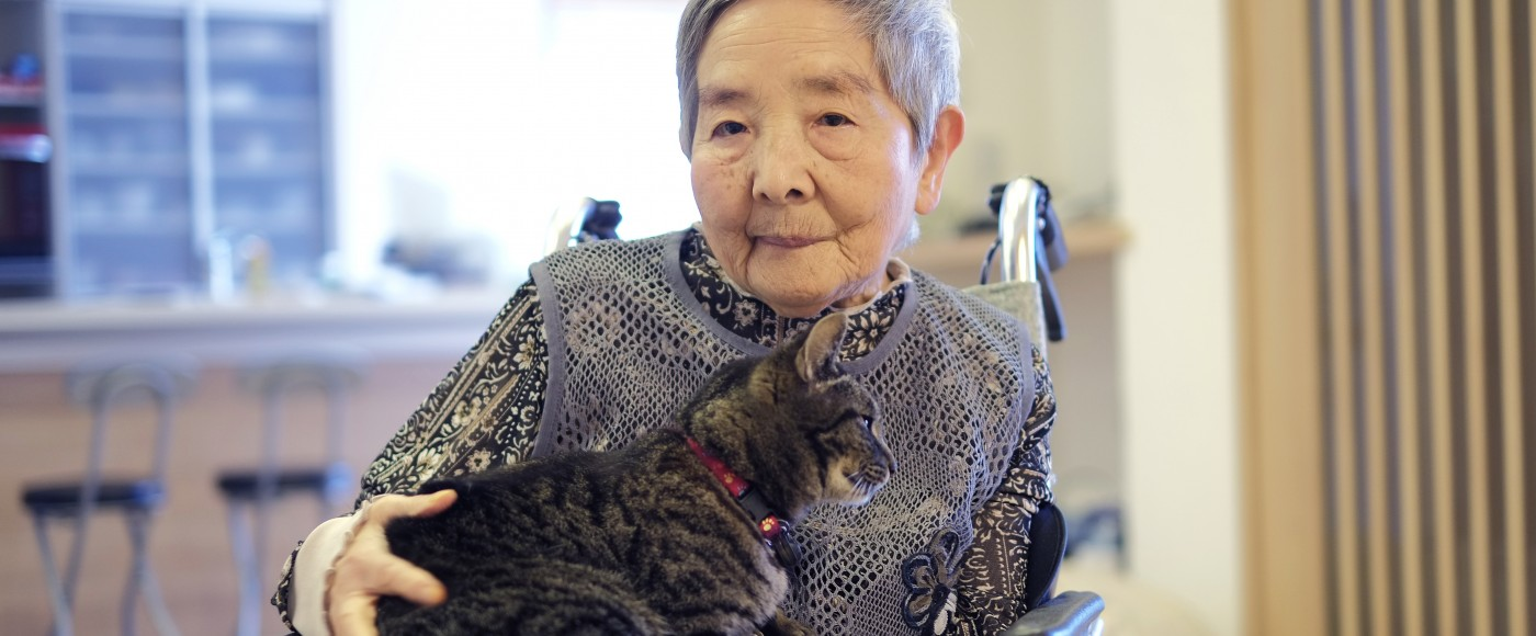 Older woman sits in wheelchair with cat on her lap